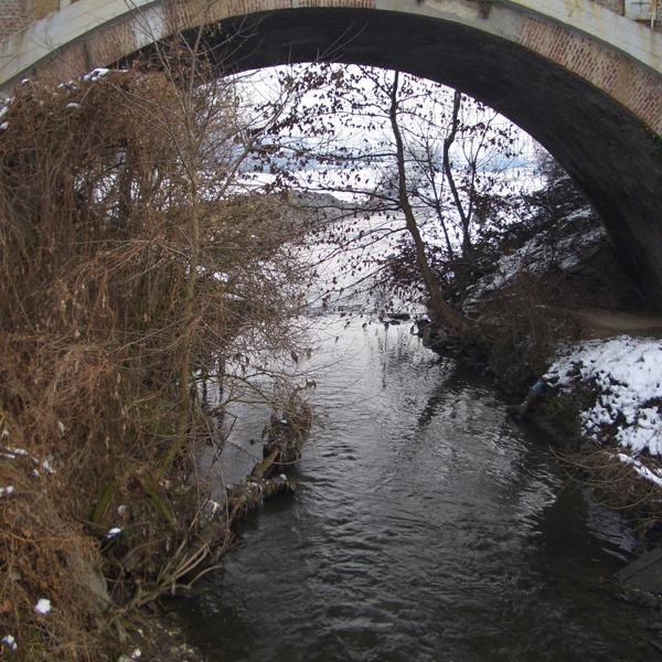 Flowing river underneath a bridge
